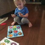 Blond toddler doing fish puzzle