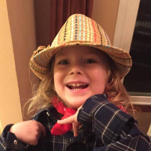 4-year-old blond boy dressing up in hat and bandana