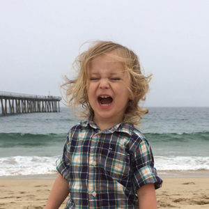 Blond 3-year-old boy screaming at the beach