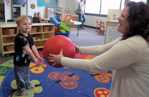 Young child catches large red ball with both hands